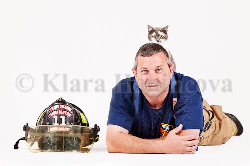 Calico cat sitting on fireman back